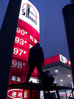 Workers change the oil price signboard in a Sinopec station in Beijing, China. Mainland oil prodcuer overtakes Exxon to become world's biggest firm by market value..
