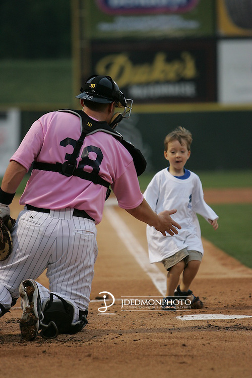 Charlotte Knights catcher high fives a young fan as he makes the bases during a pre game promotion. The Knights wore pink to honor Breast Cancer Awareness.