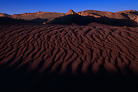 Desolate beauty of the Valle De La Luna (Valley of the Moon) results from sculpting by wind and water over millions of years. Floods and wind have left an array of oddly shaped polychrome desert land forms. The view from a tall dune shows a stark landscape. The Atacama Desert in Chile is known as the driest place on earth where parts of the desert go for more than a century without recordable precipitation.