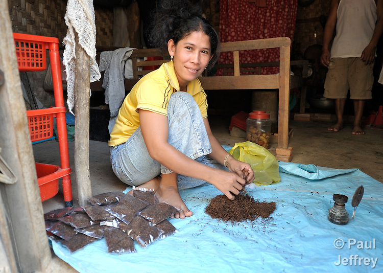 A woman repackages tobacco for sale in the Phnom Penh neighborhood of Sen Rikreay. Many people in this community are infected or affected by HIV and AIDS, and Buddhist monks and other religious meet with them regularly to mediate and discuss their challenges.