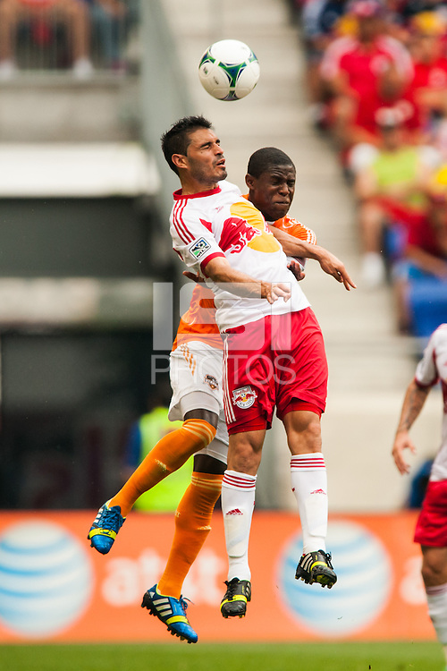Fabian Espindola (9) of the New York Red Bulls goes up for a header with Kofi Sarkodie (8) of the Houston Dynamo. The New York Red Bulls defeated the Houston Dynamo 2-0 during a Major League Soccer (MLS) match at Red Bull Arena in Harrison, NJ, on June 30, 2013.