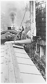 Photo taken from box car roof looking at locomotive from the rear.  Shows fireman loading water into tender tank.<br /> D&amp;RGW  Silverton Branch, CO  Taken by Henry, W. - 1959