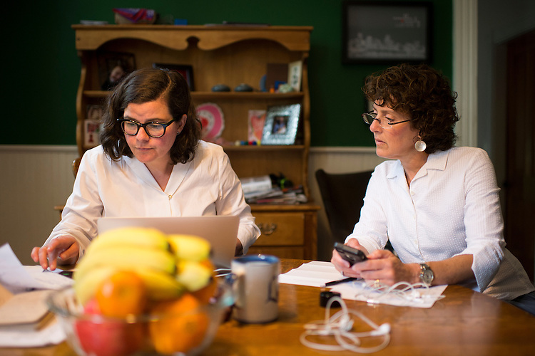 UNITED STATES - MAY 5: Democratic campaign consultant Martha McKenna, left, and Maryland House Del. Shelley Hettleman coordinate volunteer efforts at McKenna's dining room table in Baltimore on Tuesday, May 5, 2015. In the wake of the unrest in Baltimore, McKenna organized food deliveries, and on this day, flower deliveries to senior citizen facilities in the areas of the city affected by the Freddie Gray riots. (Photo By Bill Clark/CQ Roll Call)