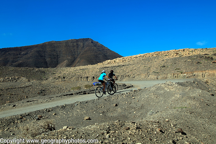 Cycling in barren landscape of Jandia peninsula Fuerteventura, Canary Islands, Spain