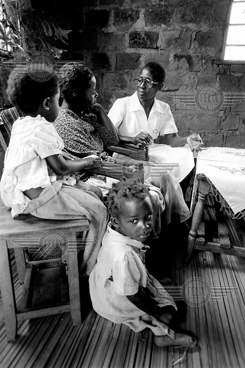 ©ÊJim Holmes / Panos Pictures..Home visit by hospital outreach worker for HIV positive woman unable to make the trip to the hospital, Uganda.