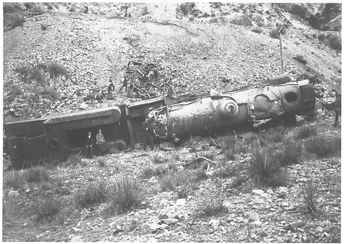 Derailed and wrecked K-27 #450 on its side in an arroyo.  Railroad track can be scene at top of photo.<br /> D&amp;RG    10/1903