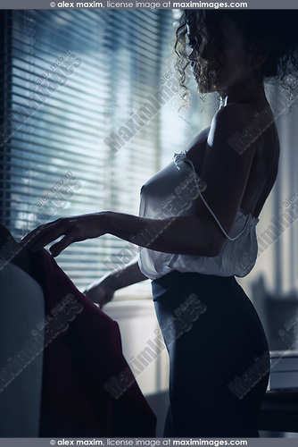 Sensual boudoir portrait of a sexy woman in a see-through sheer blouse revealing her breast and a tight black skirt standing half undressed by the window