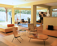 The open plan living room of this modernist house is filled with a collection of vintage designer furniture