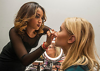 NWA Democrat-Gazette/ANTHONY REYES &bull; @NWATONYR<br /> Fatima Mejia (left) applies make-up to Kate Halverson Friday, Nov. 6, 2015 before a fashion show at the Springdale Civic Center. Northwest Arkansas Community College is sponsoring the show. It will feature designs from Gatsby's Boutique of Fayetteville, Cinderella's Boutique of Rogers and designs from Raul Rulli Torres, a NWACC graduate. Torres has shown in New York and was featured in Latino Fashion Week 2014 Dallas. All proceeds from the show benefit the college's scholarship fund.