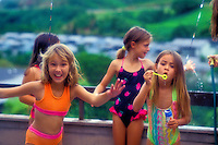 Girls having fun playing with bubbles and liquid soap