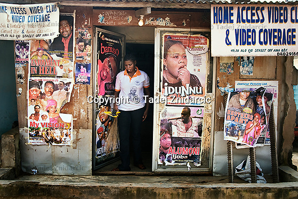 Storekeeper walks out of a local video store that sells and rents Nollywood movies on video cassettes, CDs and DVDs. Once shot, the movie is quickly edited and then replicated into hundreds of thousands of copies to be sold or rented directly as DVDs and VHS in markets, video clubs and street stores.