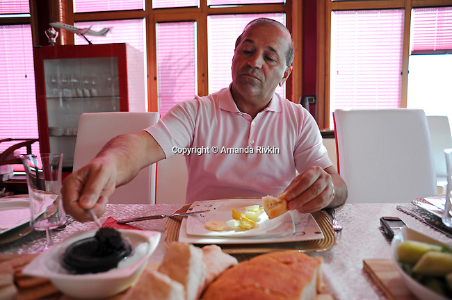 Ibrahim Ibrahimov, an Azerbaijani oligarch and billionaire, helps himself to caviar for breakfast in one of several houses on his Caspian seaside property he used to inhabit with his family in the Garadagh region just southwest of Baku, Azerbaijan on July 18, 2012.  Ibrahimov is the developer behind the Khazar Islands artificial islands project; in his private life, he enjoys building a home for his family, moving in, and then quickly tires of the property before building a new home on an adjacent lot on his seaside lands.