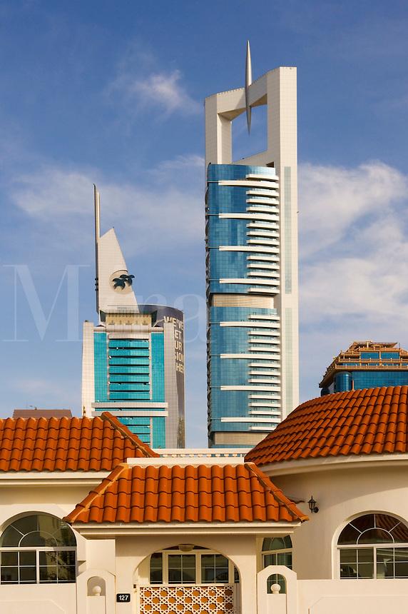 Private house and tall modern tower blocks on Sheikh Zayed Road, the main road between Dubai and Abu Dhabi. Dubai. United Arab Emirates.