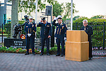 Merrick, New York, USA. 11th September 2015. At podium, Deacon JOE ZUBROVICH, of Curé of Ars Roman Catholic Church in Merrick, begins invocation as 3 Merrick and NYC firefigthters, next to 9/11 statue momument, start to remove their dress uniform white caps  during Merrick Memorial Ceremony for Merrick volunteer firefighters and residents who died due to 9/11 terrorist attack at NYC Twin Towers. Ex-Chief Ronnie E. Gies, of Merrick F.D. and FDNY Squad 288, and Ex-Captain Brian E. Sweeney, of Merrick F.D. and FDNY Rescue 1, died responding to the attacks on September 11, 2001.