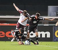 DC United midfielder Andy Najar (14) gets fouled by Colorado Rapids midfielder Jamie Smith (20) while defender Perry Kitchen gets control of the ball.   DC United tied The Colorado Rapids 1-1, at RFK Stadium, Saturday  May 14, 2011.