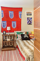 A single bed with a fur bed cover in a boy's bedroom. Football memorabilia adorns the walls.
