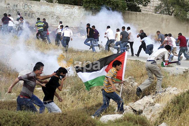 Israeli soldiers fire tear gas canister to disperse Palestinian protesters from the village of Bet In, north of Ramallah, as they hold up their national flag during protest against Israeli occupation on June 11, 2010 near the Jewish settlement of Beit El. Photo by Eyad Jadallah