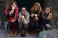 Michael McCollum.3/19/13.Four young ladies from Holland enjoy gelato cones in a doorway, near the market in Florence.