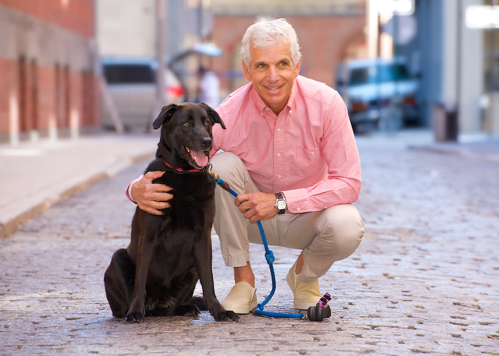 Outdoor portrait of man with dog on cobblestone street in Tribeca.