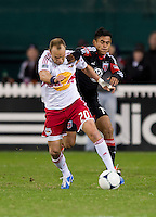 Andy Najar (14) of D.C. United fouls Joel Lindpere (20) of New York Red Bulls during the game at RFK Stadium in Washington DC. D.C. United tied New York Red Bulls, 1-1.