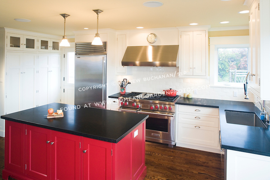 A bright red island stands out against the painted white cabinets in this unique kitchen.