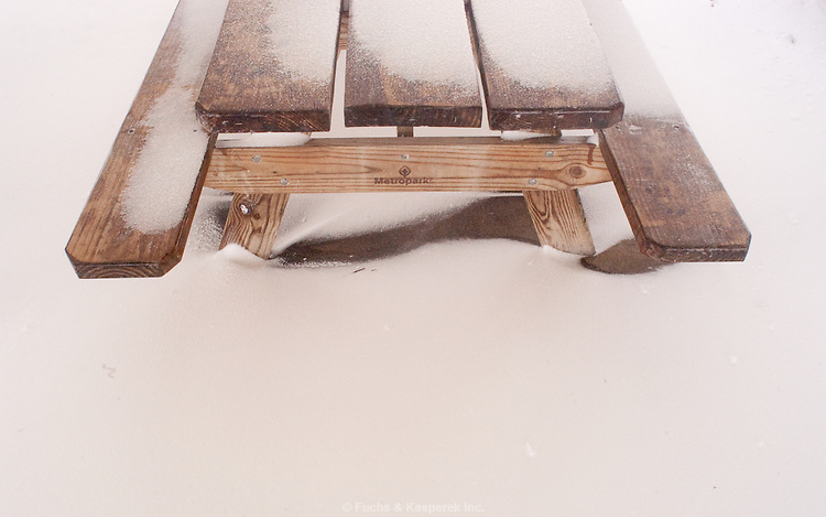 Drifting snow surrounds a picnic table inside a pavillion.