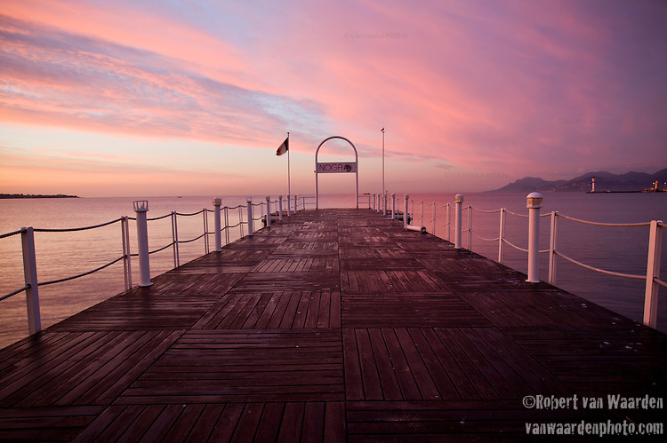 A boardwalk in Cannes, France during a pink sunrise.