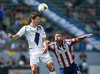 CARSON, CA - March 17, 2013: LA Galaxy defender Omar Gonzalez (4) heads the ball past Chivas forward Juan Agudelo (11) during the LA Galaxy vs Chivas USA game at the Home Depot Center in Carson, California. Final score LA Galaxy 1, Chivas USA 1.