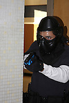 Male police officer in training holding a paint ball simulated gun clearing a school shooting scenario