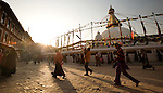 People walk around Boudhanath Stupa (or Bodnath Stupa) the largest stupa in Nepal, as the sun sets in Kathmandu.