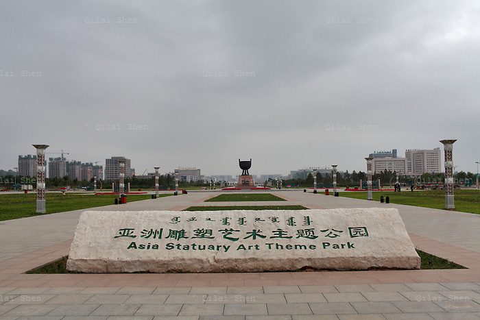 """A sign welcomes visitors to the Asia Statutory Art Theme Park in Kangbashi New District of Ordos City, Inner Mongolia, China on 16 August, 2011. With an investment of over 161billion USD from the local government and revenue from the region's rich coal deposits, enough buildings have risen on the site of an old desert village to hold at least 300,000 residents, complete with ultra modern facilities and grand plazas. The district however is less than 10% occupied, dubbed the """"ghost city"""", Kangbashi epitomizes China's real estate bubble and dangers in mindless investment fueled economic  growth. In 2011, the real estate price of Ordos city has dropped over 70%."""