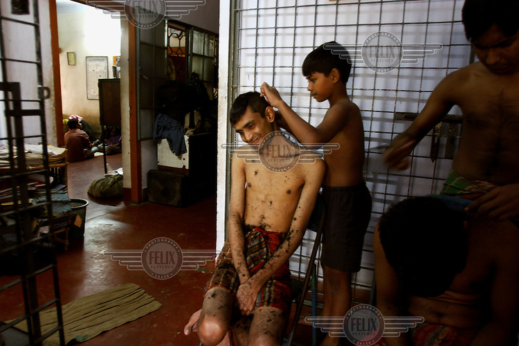 A newly-admitted addict has his head shaved at a drug rehabilitation centre. The young boy cutting his hair is himself being treated at the clinic....
