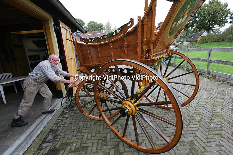 Foto: VidiPhoto<br /> <br /> EEMNES - Wagenmaker Toon Wortel uit Eemnes, de laatste wagenmaker van Nederland tussen replica's van boerenwagens zoals ze 400 jaar geleden in Nederland rondreden. Ook het ijzerwerk aan de wagens, het houtsnijwerk en het schilderwerk wordt door Wortel verzorgd. Ondanks dat er tienduizenden euro's voor de wagens worden geboden, wil Toon zijn 'kindjes' niet verkopen. Ze staan daarom allemaal in zijn eigen kleine museum in Eemnes. Jaarlijks komen er duizenden bezoekers, van jong tot oud. Met de bouw van een wagen is soms 2000 uur werk gemoeid. Alles heeft de wagenmaker zichzelf moeten aanleren. Boerenwagens werden vroeger niet alleen gebruikt voor transport, maar ook om er mee naar de kerk te gaan. Vandaar het soms het uitbundige houtsnijwerk en versiering.
