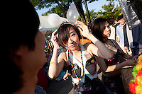 A woman wearing a dress made of condoms and wearing inflated condoms in her hair at Tokyo Rainbow Pride festival, Yoyogi Park, Tokyo, Japan. Sunday April 27th 2014 This was the third year this annual gay-pride event has been held in Japan capital.with food, fashion and health care stalls and musical performances set up in Yoyogi Park event square and a colourful parade around Shibuya at 1pm.