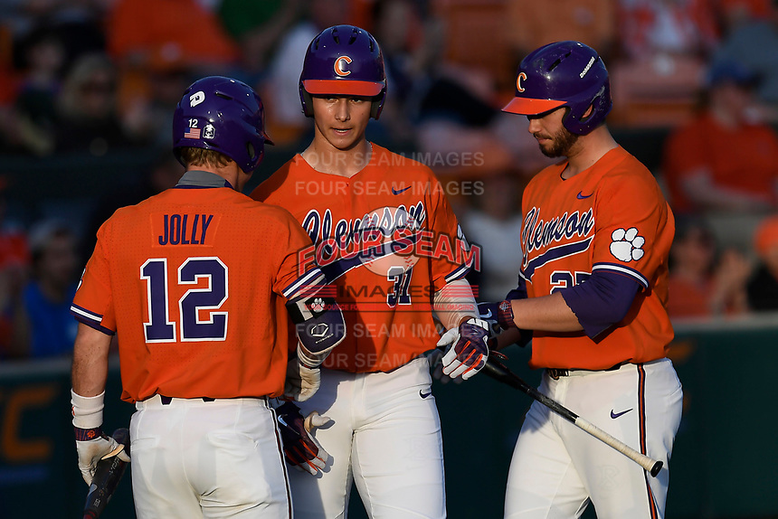 Center fielder Bryce Teodosio (31) of the Clemson Tigers is congratulated by Robert Jolly and Chris Williams after scoring his first collegiate run in a game against the William and Mary Tribe on February 16, 2018, at Doug Kingsmore Stadium in Clemson, South Carolina. Clemson won, 5-4 in 10 innings. (Tom Priddy/Four Seam Images)
