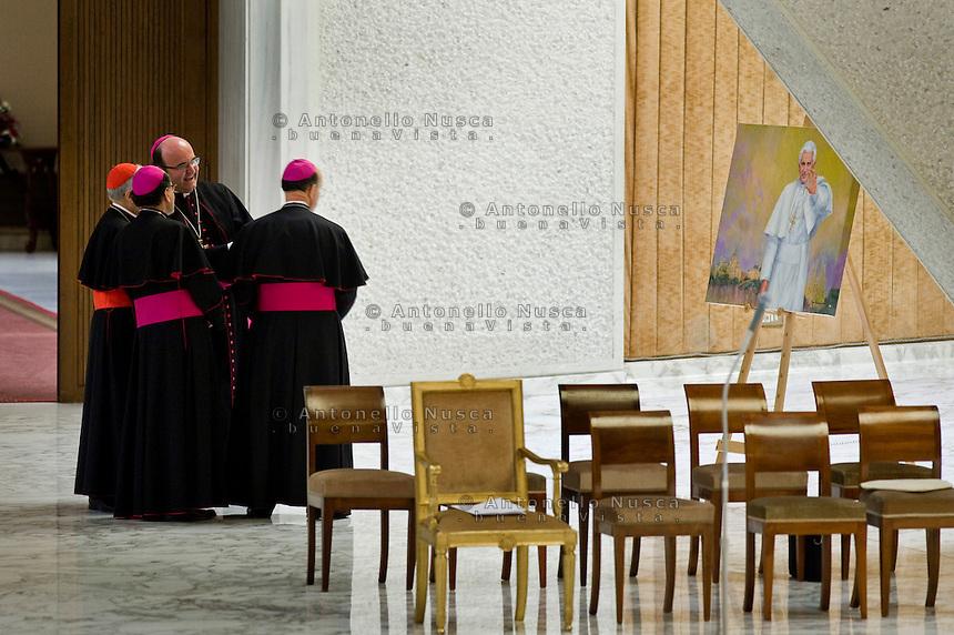Cardinali e Vescovi nell'Aula Paolo VI ammirano un ritratto di Benedetto XVI