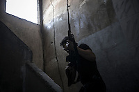 In this Monday, Oct. 29, 2012 photo, a rebel sniper sneaks through house building as he takes his fire position during clashes between rebel fighters and the Syrian army in the nearby Castel Harami battlefield in the Jdeide district of Aleppo, Syria, as heavy shelling and fighting were report during the last day of Eid celebration. (AP Photo/Narciso Contreras).