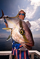 Maldives November 2008. Fisherman in his 50s holding an Amberjack (Seriola rivoliana), a member of the carangide family found in all temperate waters.