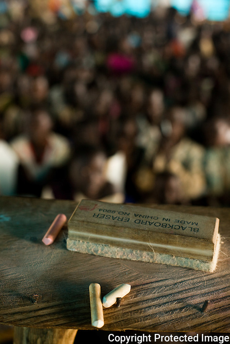 Chaulk and eraser on a teachers stand in a makeshift school in south sudan. There are hundreds of children in each overcrowded class.