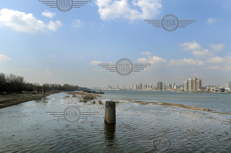The Yalu River, that forms the border between China and North Korea, to the right the wealthy Chinese city of Dandong, and to the left is the barren North Korean side.