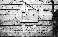 East Germany, former GDR, East Berlin, house wall with holes from bullet shots from the final battle between soviet Red Army and German Nazi soldiers in 1945 during second world war, frame with text PAX peace