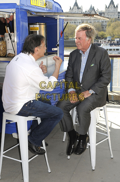 Raymond Blanc & Terry Wogan.being filmed for the BBC at the Real Food Festival, Southbank, London, UK, May 3rd 2013..full length sitting on stool white chef suit jeans  grey gray blue shirt jacket bar hand gesture .CAP/PP/BK.©Bob Kent/PP/Capital Pictures