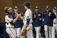 Michigan Wolverines catcher Joe Donovan (0) congratulates pitcher Jack Weisenburger (48) after defeating the Michigan State Spartans in the NCAA baseball game on May 7, 2019 at Ray Fisher Stadium in Ann Arbor, Michigan. Michigan defeated Michigan State 7-0. (Andrew Woolley/Four Seam Images)