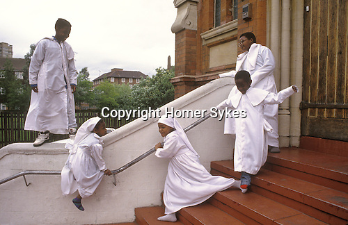 Brotherhood of the Cross and Star London. Children play on the steps of the church in Elephant and Castle south London during a day long Sunday Service. This semi Christian church was founded by Olumba Olumba Obu. from A STORM IS PASSING OVER a Look at Black Churches in Britain. Published by Thames and Hudson isbn 0 500 27826 1