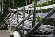 Side view of footbridge along the Thoreau Falls Trail at North Fork Junction in Pemigewasset Wilderness of Lincoln, New Hampshire. This bridge crosses the East Branch of the Pemigewasset River, and it has a noticeable tilt.