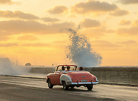 The sun sets as classic cars travel along the Malecon in Havana, Cuba.
