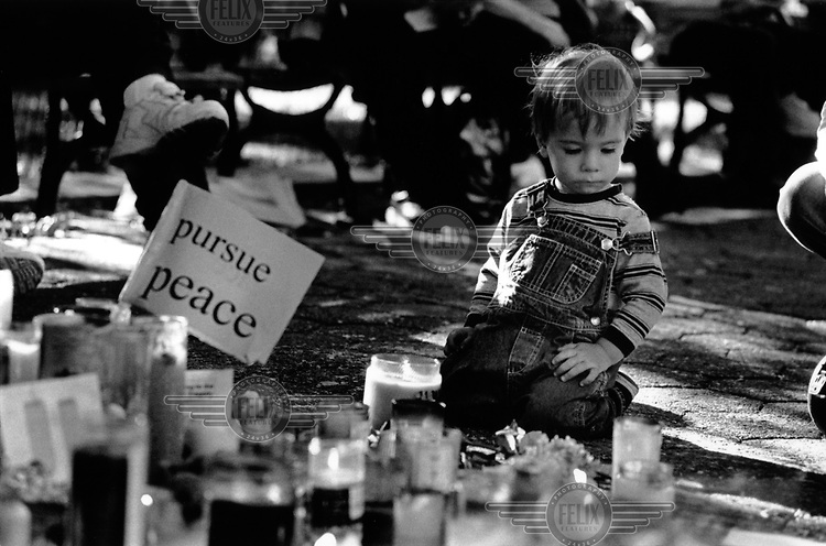 A child kneels by candels Union Park Square in Manhattan, New York City, to commemorate the missing and dead from the 9/11 terrorist attack on the World Trade Centre.
