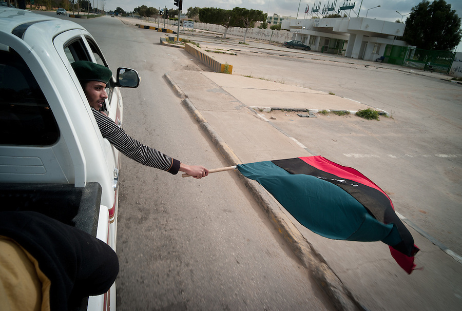 Monarchy era flag flys driving to cemetery for a funeral in Benghazi, Libya.