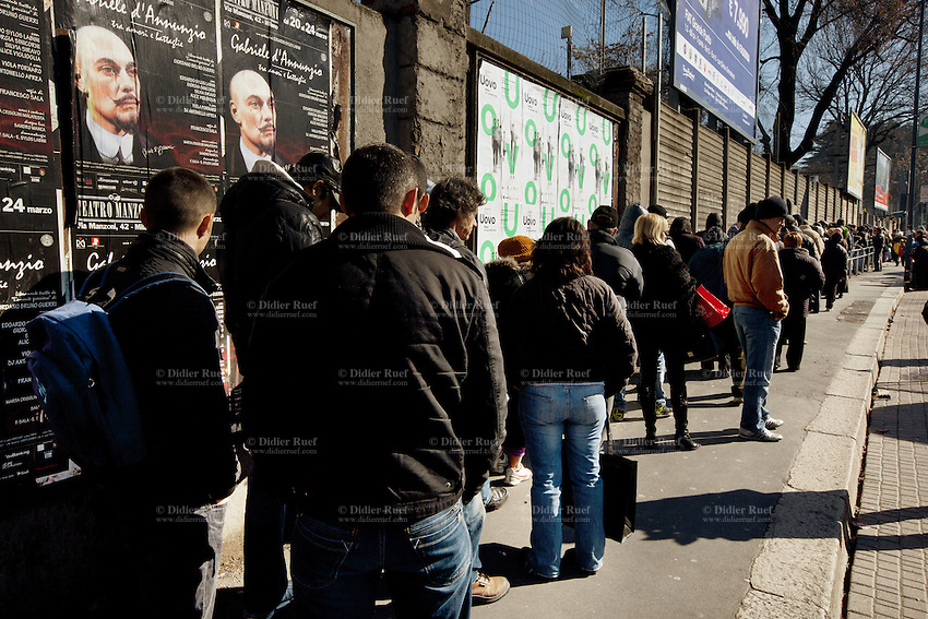 Italy. Lombardy region. Milan. A free food distribution takes place daily at the lay association: Pane Quotidiano. People queue on line and wait outside before the morning openig. Thousands of people receive daily bread, milk, yoghurt, vegetables, fruits,..Theater billboard. A play by the author Gabrielle d'Annunzio. Gabriele D'Annunzio (12 March 1863 - 1 March 1938), was an Italian writer, poet, journalist and playwright. 19.03.13 © 2013 Didier Ruef