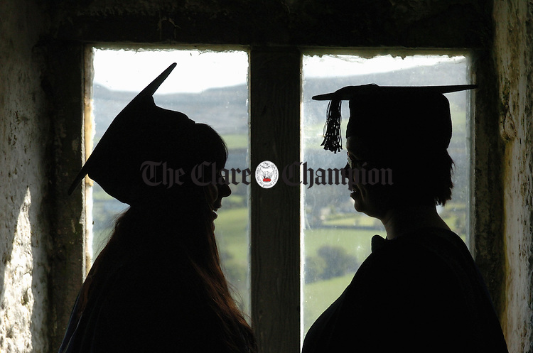 Monique Given and Rae Le Grone are silhouetted in the window of Newtown castle againste a backdrop of Limestone hills at the conferral of Ireland's first Master of Fine Arts Degrees by NUI Galway at the Burren College of Art in Ballyvaughan. Photograph by John Kelly.